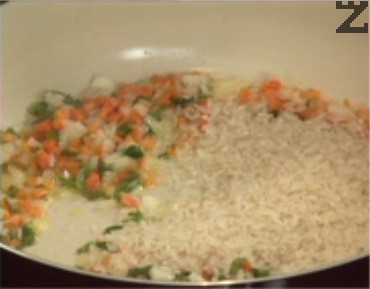 Прибавяме и почистения и измит ориз, запържваме докато стане стъклен. Оттегляме от котлона, поръсваме с червен пипер.