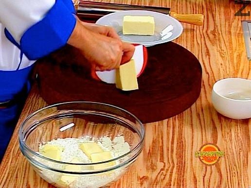 Изсипваме брашното в купа и добавяме нарязаното на парченца масло. Разбъркваме, докато брашното стане на трохи
