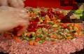 Разпределяме нарязаните на кубчета моркови, гъби, чушки, сварени яйца и кисели краставички. Поръсваме със замразения грах, настъргания кашкавал и листата магданоз.