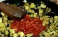 Добавяме едро нарязаните скилидки чесън, двата вида домати, поръсваме със сол и захар. Задушаваме около 10 мин., при нужда добавяме гореща вода.