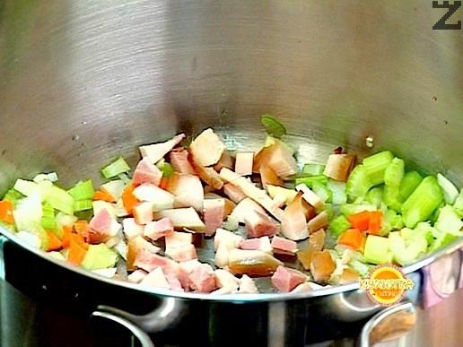 В дълбока тенджера се загрява зехтина и запържват на умерен огън лука и морковите за 30 секунди.Прибавя се чесъна, целина и бекона нарязан на кубчета.