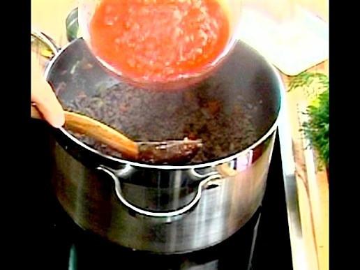 Тогава се добавят пюрираните домати, слага се кубче телешки булъон и се налива 200 мл ( 1 чаша ) гореща вода. Разбърква се посолява се и сместа се оставя да къкри под капак за около 20-30 минути. След като отнемем съда от огъня, прибавяме риган.