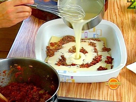 """На дъното на правоъгълна тава с големина 30х40 см се нанася тънък слой от сос Бешамел. Поставя се един пласт от корите и се нанася 1/4 от каймата. Подрежда се втори ред кори, поливат се със 1-2 черпака сос """"Бешамел, 1/4 от каймата и се реди нарязано на тънки филии сирене моцарела."""