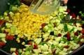 Нарязваме зеленчуците на малки кубчета. Запържваме лука и чушките, след 1 мин. добавяме тиквичката и царевицата.
