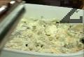 Разбиваме поотделно киселото мляко и жълтъка, смесваме двата продукта. Посоляваме, настъргваме сиренето, разбъркваме и нанасяме върху картофите. Наливаме 1 к.ч. топла вода, поливаме с олио. Печем в умерено загрята фурна за 30 мин.