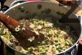 Добавяме агнешките дреболии. Бъркаме ястието докато поеме течността. Изсипваме ориза. Нарязваме подправките и ги добавяме към плънката.