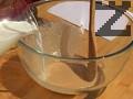 В купа поставяме маята и захарта. Разбъркваме ги добре. Прибавяме леко затопленото прясно мляко, добавяме малка част от брашното.