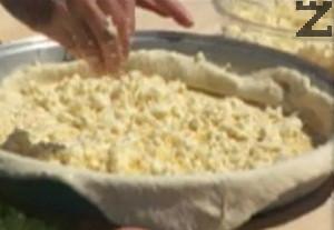 Разточваме, прехвърляме го в предварително намаслената тава. Поливаме с 1 пак. разтопено краве масло, поръсваме с натрошеното сирене.