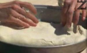 Прегъваме тестото, навиваме на руло. Разстиламе го, за да покрием дъното на тавата. При нужда поръсваме с брашно.