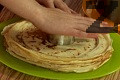 Режем с голям и малък ринг всяка от палачинковите купчини. Подреждаме в тортена чиния, като редуваме кръгове от бял и какаов блат.