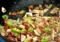В тефлонов тиган запържваме бекона за 3-4 мин. до златисто. Прибавяме нарязаните зеленчуци, пържим на умерен огън. Посоляваме, поръсваме с чубрица и черен пипер.