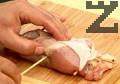Завиваме на руло. С отделената пилешка кожа покриваме отворената част на напълненото бутче. Пробождаме месото с дървено шишче, предварително потопено в студена вода.