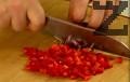 Нарязваме филето на кубчета. По същия начин режем и чушките. Наситняваме лука, смесваме съставките в купа. Обелваме и нарязваме на кубчета домата и чушката.