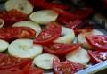 Нарязваме на шайби лука и доматите, подреждаме ги на дъното на тава. Посоляваме.