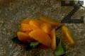 Обелваме портокала и отстраняваме ципите. Добавяме към захарния сироп и варим още около минута.