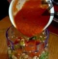 Прибавяме изстиналите чушки към бадемовата смес. Прибавяме доматения сос, поръсваме със сол и черен пипер. Поливаме със струйка зехтин, пасираме отново.
