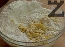 В отделен съд смесваме киселото мляко, захарта и солта. Прибавяме към брашното. Счупваме яйцата, като на едното отделяме жълтъка. Прибавяме и сместа с маята.