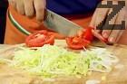 Нарязваме салатата Айсберг на ситни ивици, лука - на колелца, а домата - на едри парчета.