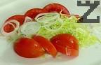 В средата на чиния за сервиране поставяме част от нарязаната салата Айсберг, парченца домат и шайби лук.