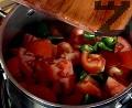 Нарязваме доматите на едри кубчета. Поставяме ги в тенджера заедно с нарязаните люти чушки.