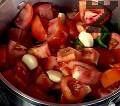 Посоляваме, поливаме с олио. Добавяме скилидките чесън. Оставяме зеленчуците да заврат, след което намаляваме огъня на средно ниво.