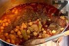 В дълбока тенджера поставяме сварения нахут и запържената смес. Прибавяме доматено пюре. Поливаме с около 1 л бульон от варения нахут. Поръсваме със сол и натрошеното кубче бульон. Подправяме с майоран, чубрица, риган и чили. Оставяме ястието да ври на умерен огън до готовност.