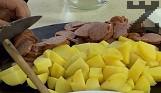 Сваряваме и обелваме картофите. Нарязваме на кубчета заедно с наденицата, а репичките - на шайби.