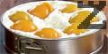Покриваме я с белени праскови от компот, поръсваме стафиди и оставяме тортата в хладилник, за да стегне.