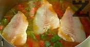 Посоляваме, поръсваме с черен пипер. Прибавяме рибните филета в тенджерата. Поставяме в загрята на 180 градуса фурна, печем докато ориза поеме течността.