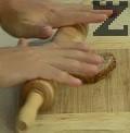 Омекотяваме и изтъняваме филийките хляб като ги притискаме няколко пъти с точилка. Покриваме с половината от тях дъното на тавата, предварително намазана с масло.