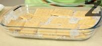 В правоъгълна тавичка с дължина около 20 см и широчина 15 см редим бисквити и крем до изчерпване на съставките.