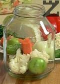 В буркана подреждаме целите корнишончета, надупчените на няколко места домати, розички карфиол и моркова, нарязан на едри парчета.