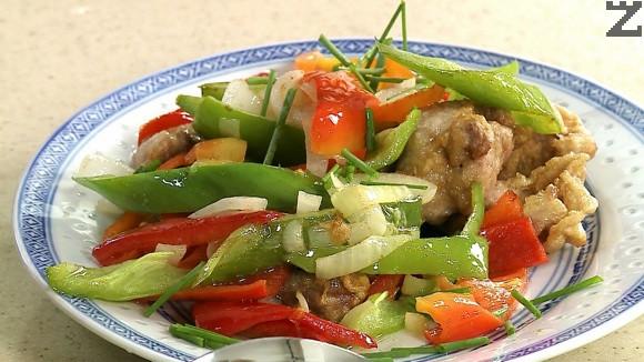 В чиния за сервиране се слага месото с пържените пиперки. Гарнира се с нарязани пера пресен лук.