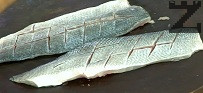 Почистваме рибата от люспите, отстраняваме вътрешностите и главата. Филетираме, като разрязваме внимателно по дължина. Изваждаме средната кост и отстраняваме коремната част. Правим няколко прореза по повърхността.