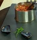 В малка тенджерка карамелизираме захарта, поставяме по 5-6 мидени ядки за всяка порция и разбъркваме добре. Пълним дълбок метален ринг последователно с чушки, карамелизирани миди, патладжан и домат. Отстраняваме ринга и върху кьопоолуто поставяме една мидена ядка. Поръсваме с наситнения магданоз. Д