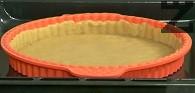 Разделяме тестото на две части. Разточваме две кръгли кори с големината на формата за печене - 24-26 см. Слагаме първата кора в силиконова форма за печене, оформяме ръб.