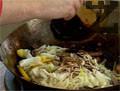 Връщаме зеленчуците при месото и поливаме със заливката. Разбъркваме и поливаме малко сусамово олио. Изсипваме запърженото месо и зеленчуци върху канапето от нудълс и декорираме с 2-3 пера пресен лук.