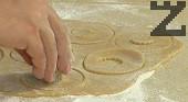 Разделяме тестото на две части, върху набрашнена повърхност разточваме дебели кори. С кръгла форма за бисквитки изрязваме тестото, като на половината от кръговете изрязваме в средата кръг с по-малка форма. За да не се лепи тестото по формите, ги набрашняваме периодично.