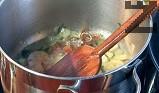 Прибавяме доматеното пюре и сухия рибен бульон. Разбъркваме периодично. Поливаме с още 100-200 мл гореща вода, поръсваме с нарязаните пера пресен лук. Поръсваме със сол и куркума. Оставяме да ври още за час на слаб огън, след което прецеждаме бульона.