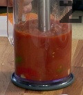 Обелваме, отрязваме и наситняваме колелцата джинджифил. Поставяме в купа заедно с едро нарязаните чушки и домати. Поръсваме със сол и захар, пасираме добре.