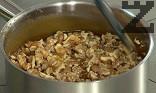 Разбъркваме добре и поставяме начупените орехови ядки.