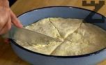Намазняваме я, поставяме тестения кръг и нарязваме на триъгълни парчета като торта. Оставяме да втаса за кратко. Печем в сгорещена на 180 градуса фурна за 15-20 мин., докато се зачерви. Изваждаме от фурната, завиваме с кърпа за кратко и сервираме.