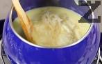 След разтопяването им добавяме настърганото на едро ренде сирене Грюер. Изчакваме и неговото разтопяване, като разбъркваме непрекъснато.