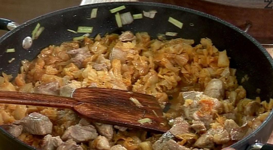 В същата тепсия изсипваме киселото зеле, свинското месо и поръсваме черен пипер. Добавяме люти чушки, разбъркваме и наливаме топла вода.