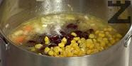 Поливаме със зеленчуковия бульон, добавяме боба и царевицата. Оставяме ястието да къкри на огъня, докато поеме течността.
