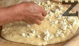 Поливаме първия лист с 1-2 струйки олио, поръсваме с натрошеното сирене.
