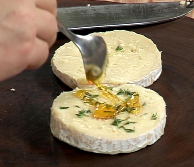 """Разрязваме питата """"Камембер"""" на две равни части. Нарязваме на ситно ½ скилидка чесън, накъсваме листенца прясна мащерка и ги втриваме в сърцевината на сиренето. Поръсваме пчелен мед и съединяваме двете половина на питата."""