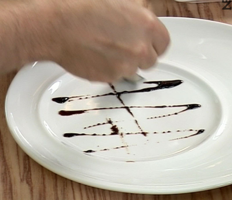 В чиния правим украса от балсамова редукция, поставяме запеченото сирене в бекон. Декорираме предястието с клонка мащерка и поливаме с редуцирания балсамов сос.