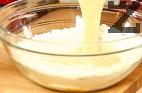 Към купата с жълтъците добавяме брашното, разбъркваме с помощта на шпатула. Поръсваме с ваниловата захар и канелата. Разбъркваме отново, като добавяме банановата каша и останалата част от прясното мляко.