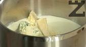 Приготвяме соса. В тенджерка поставяме сметаната. След като се сгорещи, поръсваме с чеснов прах и сол, добавяме натрошеното синьо сирене. Варим на бавен огън, докато сиренето се разтопи. Прибавяме на тънка струйка към месото и зеленчуците, като разбъркваме непрекъснато.